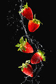 Strawberries in water splash isolated on black background