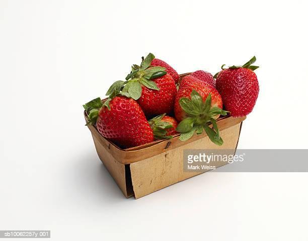 Strawberries in wooden basket against white background