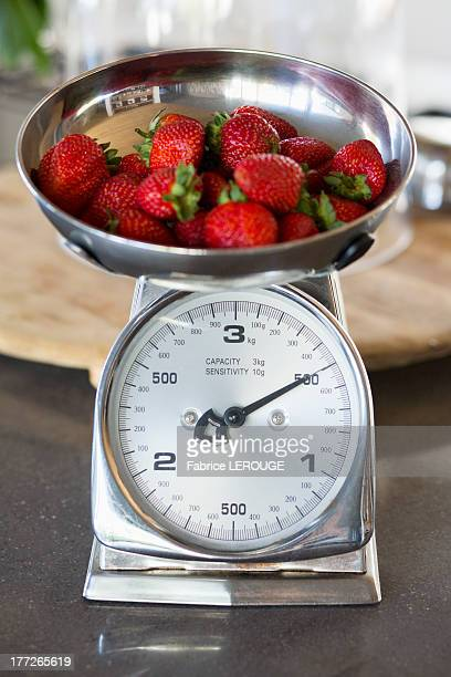 Strawberries on a weighing scale at a kitchen counter