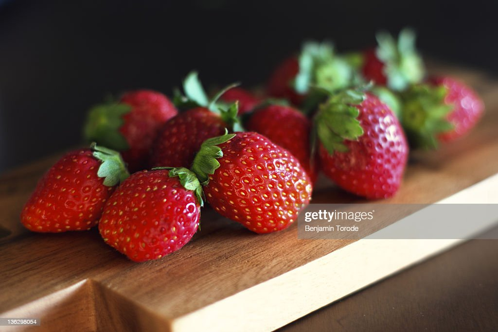 Strawberries on wooden cutting board : Stock Photo