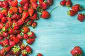 Summer fruit food frame. Strawberries over turquoise blue painted wooden background. Top view, copy space