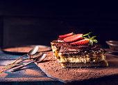 strawberries tiramisu cake with three spoons on dark wooden background