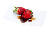Strawberries with balsamic vinegar on white background