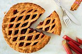 Strawberry and rhubarb pie with cut piece on a marble background, overhead scene