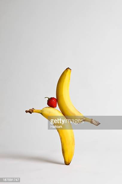 A strawberry balancing between two bananas