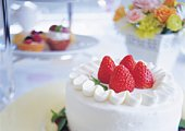 Strawberry cake and flowers on table