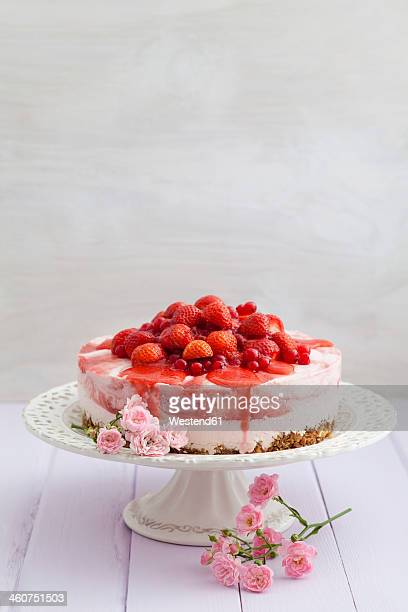 Strawberry cheesecake with fresh strawberries and redcurrants on wooden table, close up