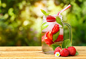 strawberry lemonade in mason jar on wooden table with blurred sunshine natural background. Summer refreshing drink. Cold detox water. Strawberry cocktail. Copy space