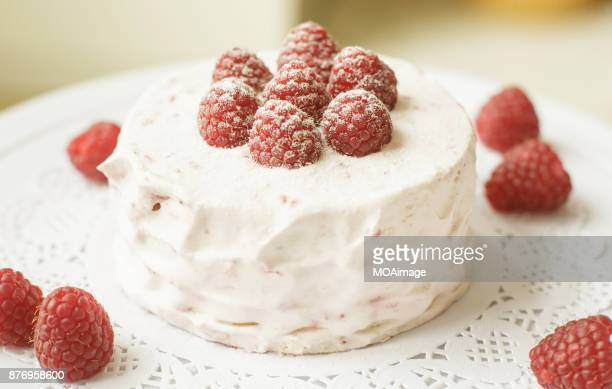 A strawberry cream cake on a cake stand is put on a wooden table