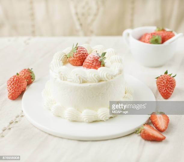 A strawberry cream cake on a white plate is put on a wooden table