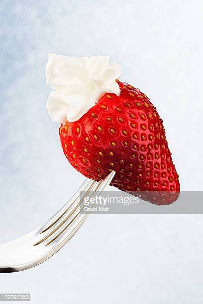 Strawberry dipped in whipped cream on fork