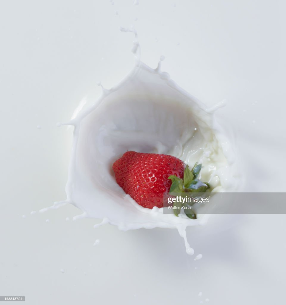 Strawberry dropping into milk : Stock Photo