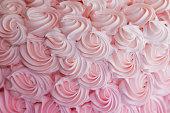 Strawberry frosting swirls on a cake.