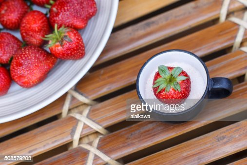 Strawberry in a cup of milk on bamboo table : Stockfoto