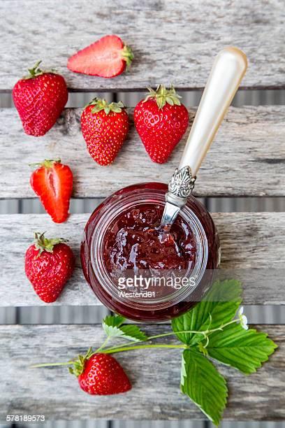 Strawberry jam in glass, strawberries on wood