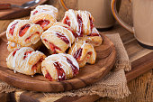 Pile of strawberry pastries on a wooden plate with coffee mugs in background