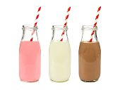 Strawberry regular and chocolate milk in bottles with striped straws isolated on white