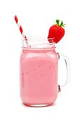 Pink strawberry smoothie in a mason jar glass with straw isolated on white