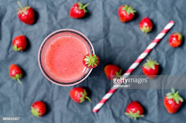Strawberry smoothie in glass, strawberries and drinking straw