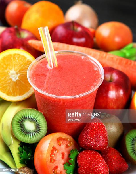 A strawberry smoothie surrounded by fruits