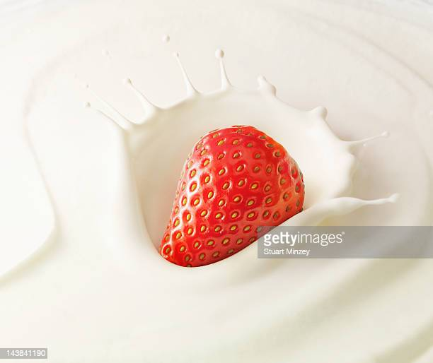 Strawberry splashing into cream