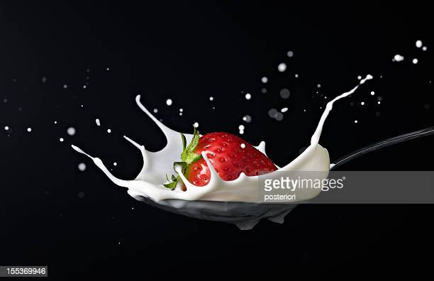 strawberry splashing into spoon full of milk