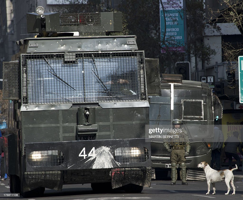 A stray dog stands by a riot police water cannon during a demonstration against the government of Chilean President Sebastian Pinera in Santiago on July 11, 2013 in Santiago. Since the beginning of the massive marchs of students protesting against the education system in 2011, scores of stray dogs happily participate in all the clashes with riot police, playing under the jets of the water cannons and accompanying the students whilst they are chased by police. In Santiago there are about 500,000 stray dogs, according to municipal authorities.