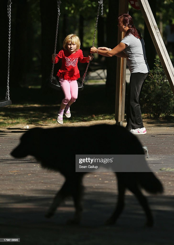 A stray dog wanders past a little girl swinging on a playground on September 7, 2013 in Bucharest, Romania. Stray dogs are a common site in Bucharest and a pack of them recently mauled a 4-year-old boy in a park to death, promping lawmakers to consider a new measure to euthanize the animals. While Romania's economic output has risen significantly since it joined the European Union in 2007, it still lags in infrastructure development and the fight against corruption.