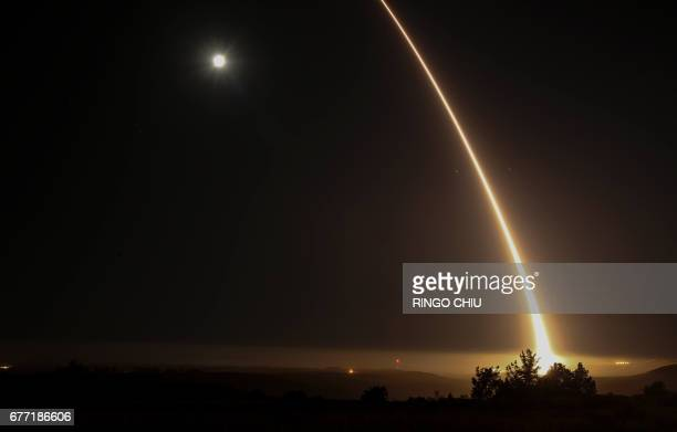 TOPSHOT A streak of light trails off into the night sky as the US military test fires an unarmed intercontinental ballistic missile at Vandenberg Air...