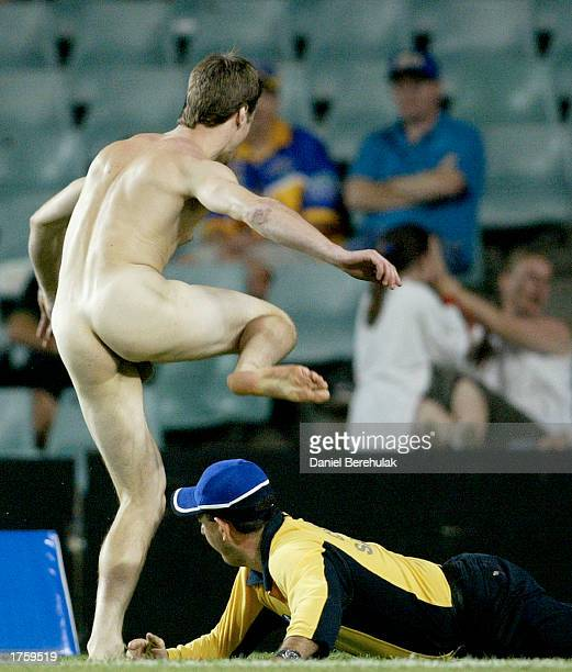 A streaker evades a security guard in the match between the St George Illawarra Dragons and Fiji during the Rugby League World Sevens Tournament held...