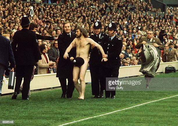 A streaker is arrested during the Five Nations match between England and Wales in 1976 at Twickenham in London