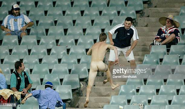 A streaker is confronted by a spectator in the match between the St George Illawarra Dragons and Fiji during the Rugby League World Sevens Tournament...