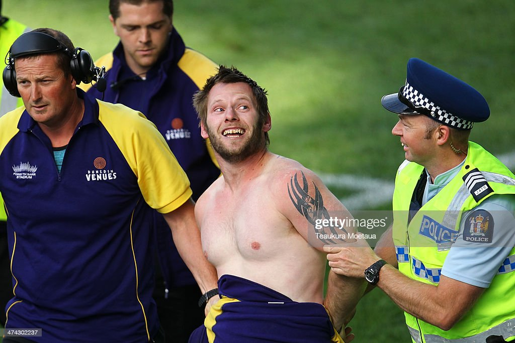 A streaker is escorted from the ground during the NRL trial match between the Brisbane Broncos and the New Zealand Warriors at Forsyth Barr Stadium on February 23, 2014 in Dunedin, New Zealand.