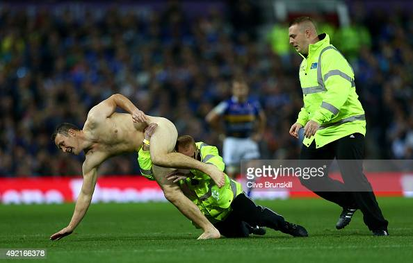 A streaker is tackled by a steward during the First Utility Super League Grand Final between Wigan Warriors and Leeds Rhinos at Old Trafford on...