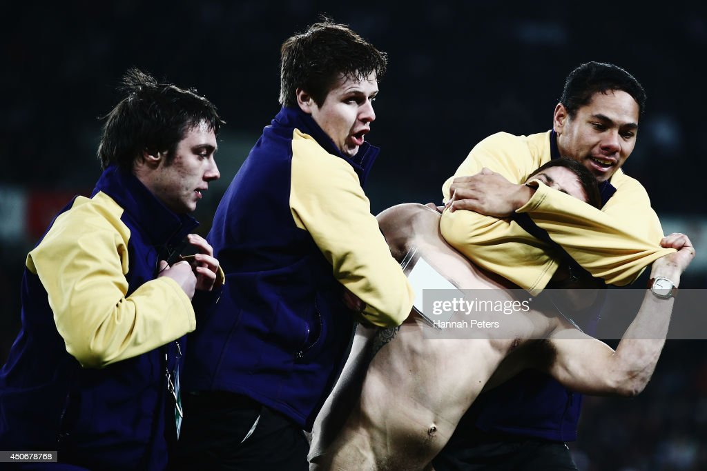 A streaker is taken from the field during the International Test Match between the New Zealand All Blacks and England at Forsyth Barr Stadium on June 14, 2014 in Dunedin, New Zealand.