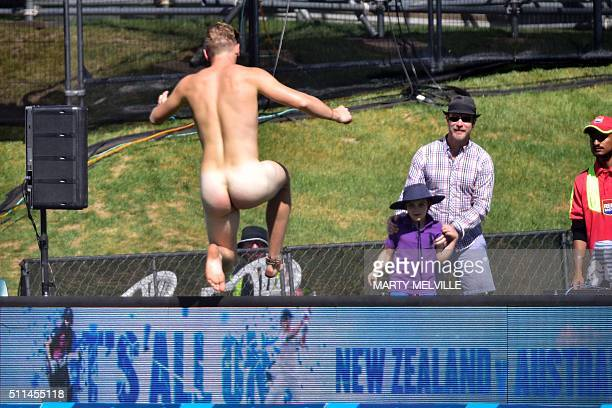 A streaker jumps over the LED signage during day two of the second cricket Test match between New Zealand and Australia at the Hagley Park in...