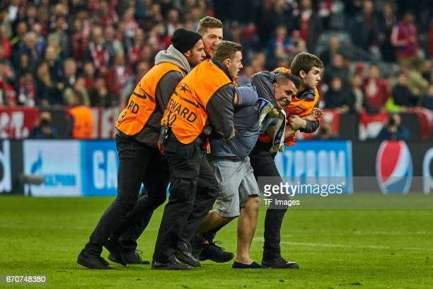 A streaker looks to avoid a security guard during the UEFA Champions League Quarter Final first leg match between FC Bayern Muenchen and Real Madrid...
