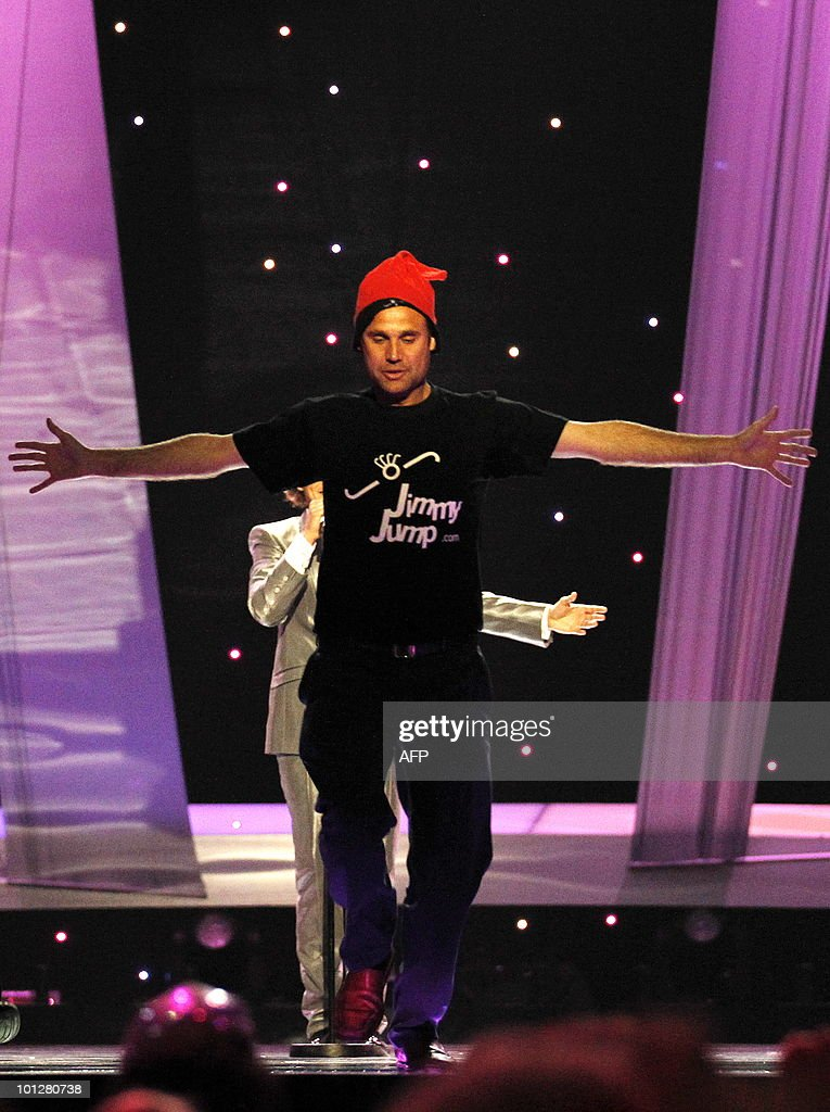 A streaker wearing a red cap and a tshirt reading 'Jimmy Jump' appears on stage as Spain's Daniel Diges performs his song 'Algo Pequeñito ' during...