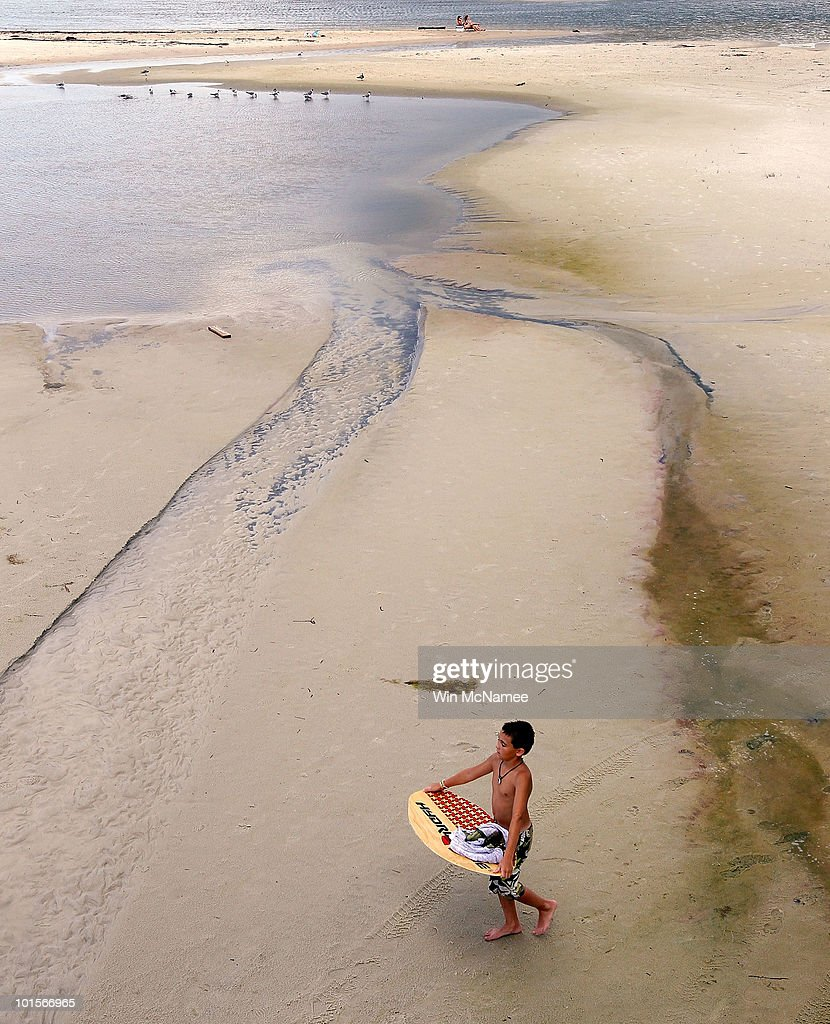 Streaks left by oil that retreated during low tide are visible on a public beach on June 2, 2010 in Dauphin Island, Alabama. Oil related to the Deepwater Horizon accident began to appear yesterday on the shores of Alabama.