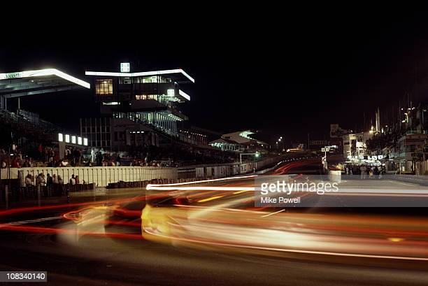 Streaks of tail lights at night along the front straight past the pits and main grandstand during the World Endurance Championship 24 Hours of Le...