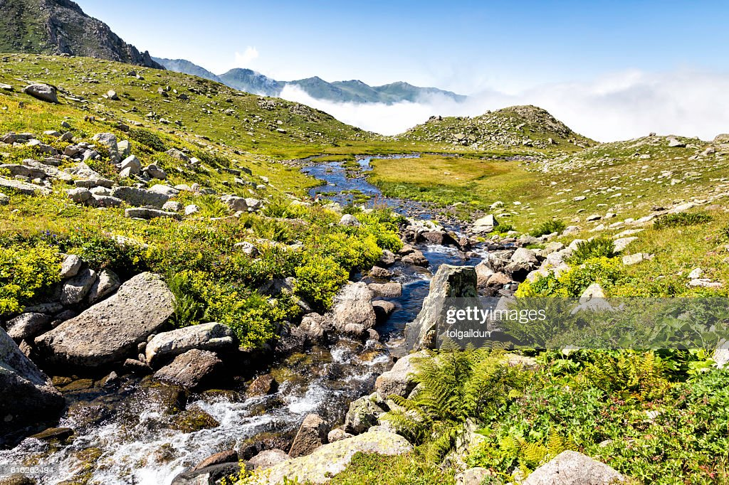 Stream flowing between the rocks with foggy Kackar mountains : Stock Photo