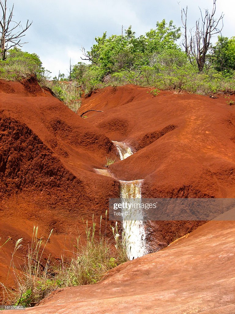 Stream flowing through red soil : Stock Photo