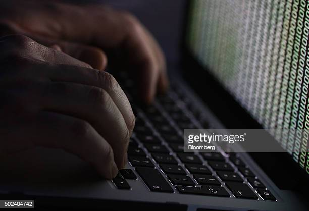 A stream of binary coding text or computer processor instructions is seen displayed on a laptop computer screen as a man works to enter data on the...