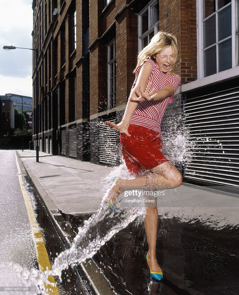 Stream of water hitting young woman on pavement : Stock Photo
