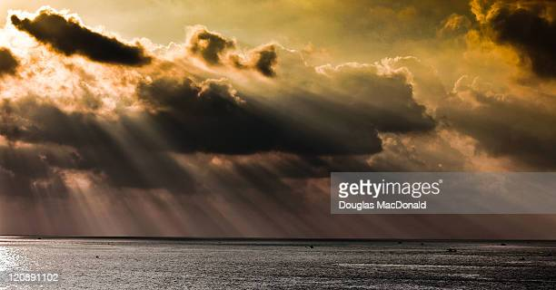 Streams of light and storm clouds at sunset