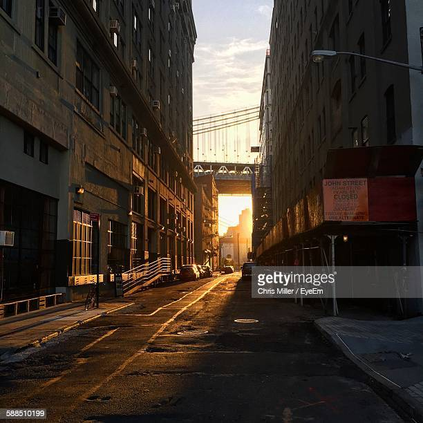 Street Amidst Buildings Leading Towards Manhattan Bridge Against Sky During Sunset
