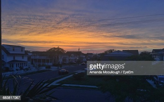 Street Amidst Houses Against Sky During Sunset