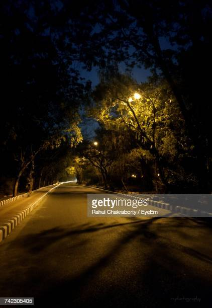 Street Amidst Trees Against Sky At Night