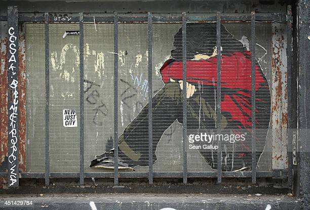 Street art behind a groundlevel grate is visible in Kreuzberg district on June 26 2014 in Berlin Germany Berlin with its long tradition of...