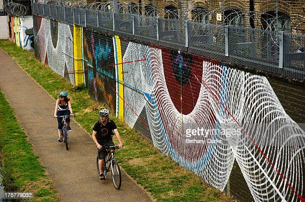 Street art by Theo Moneyless and Mark Lyken along the River Lea Navigation at Olympic Stadium on August 7 2013 in London England The mural is part of...
